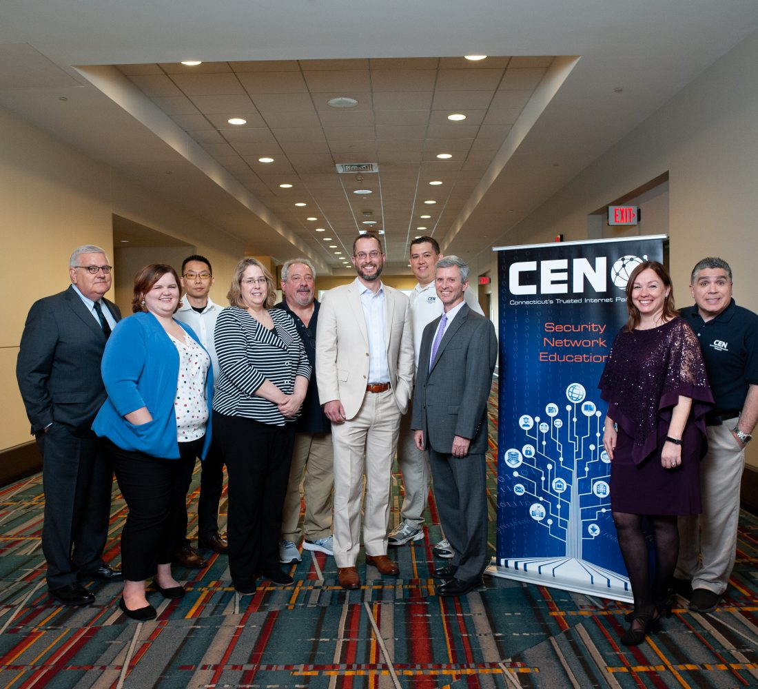 CEN employees posing as a group by a CEN poster