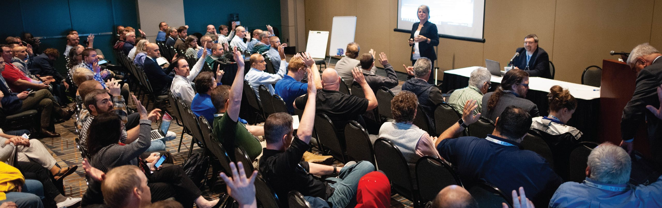 Image from the CEN Conference of a group of attendees sitting in chairs raising their hands and a woman speaking and giving a presentation